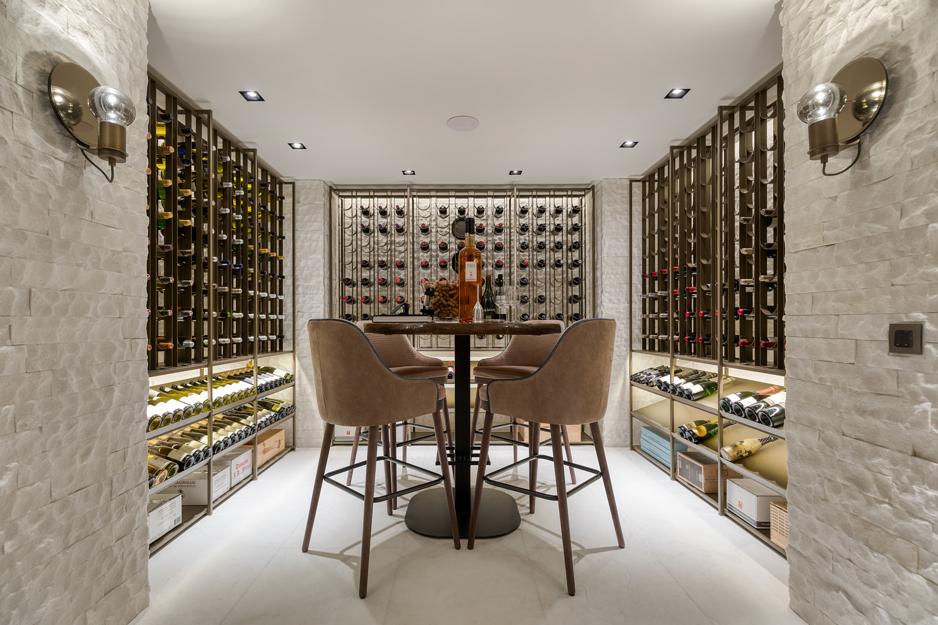 Wine cellar with cast floor and custom brazen cooled wine racks surrounded by white stone