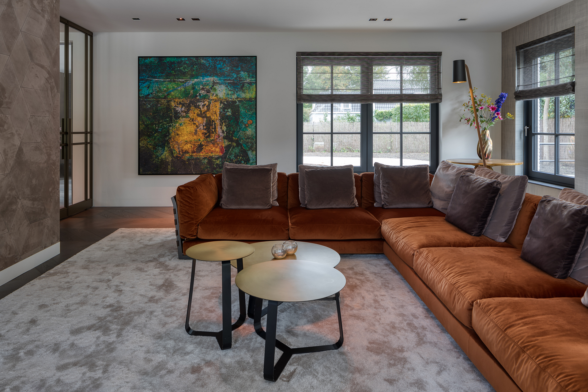 living room with large brown corner sofa on a large soft grey rug, leather and artworks adorn the walls