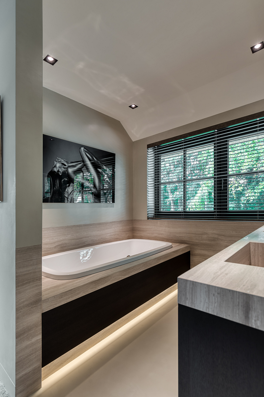 Bathroom with heated cast floor and built-in bathtub overlooking shuttered windows