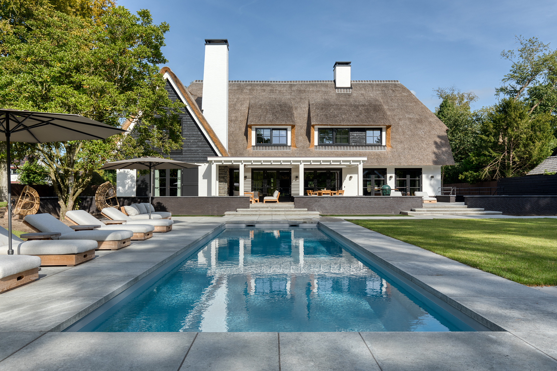 Backyard pool with cast concrete tiles with lounge beds with overlooking thatchroof estate