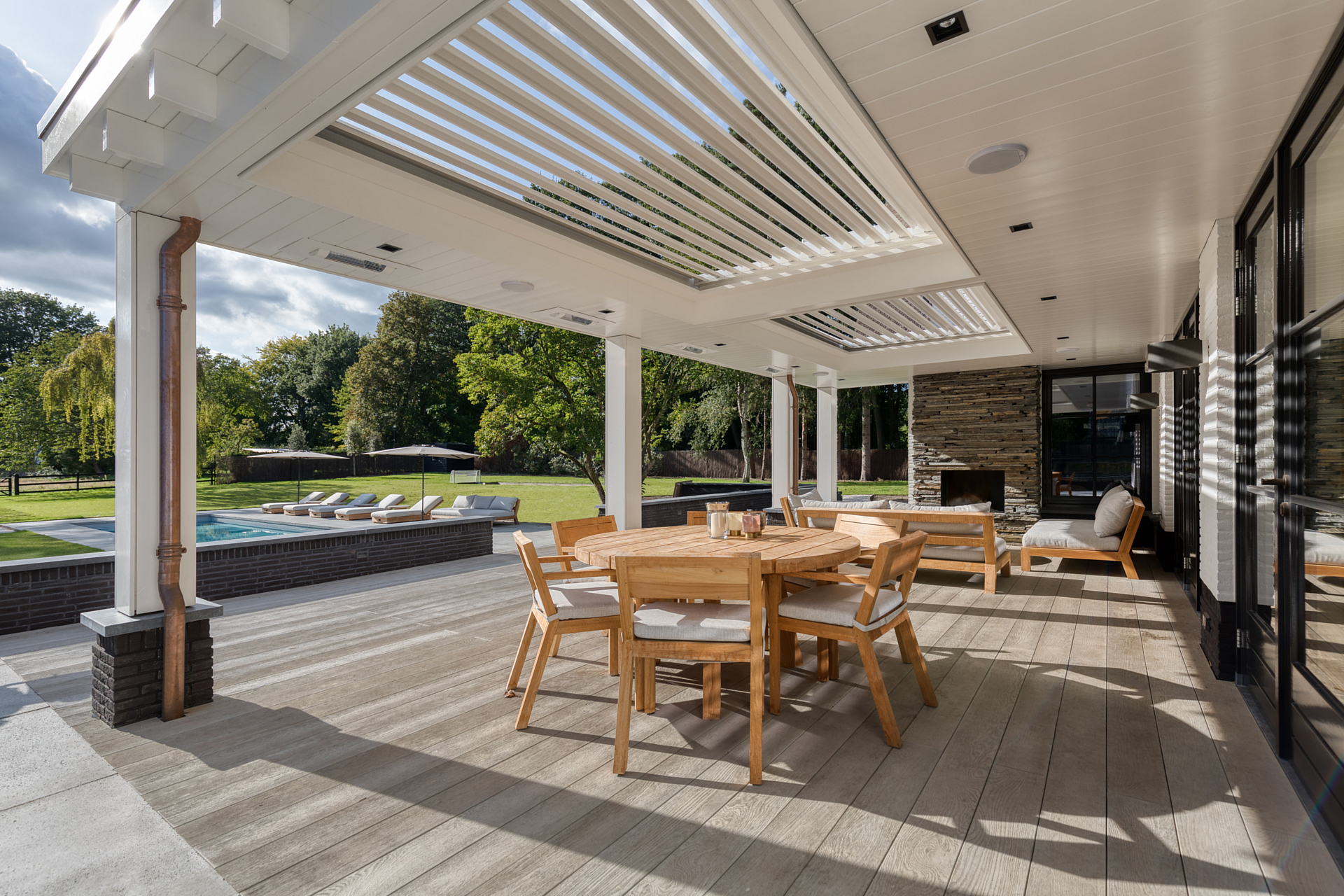 a backyard deck with sunbathed wood and overhanging automatic shutters looking out over the pool