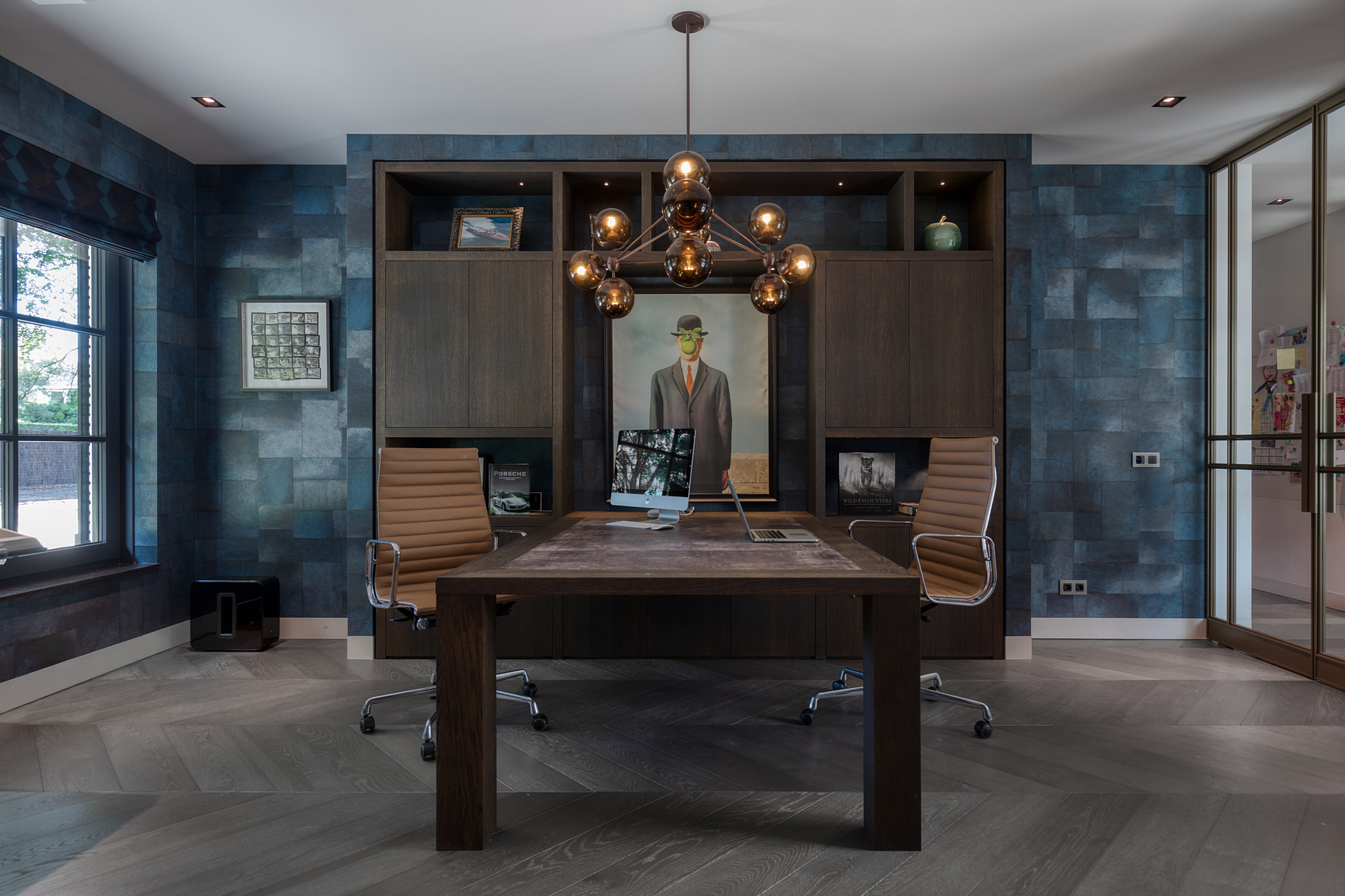 Home office with tantalizing blue wallpaper, a retro fish bulbed chandalier hangs over the desk.