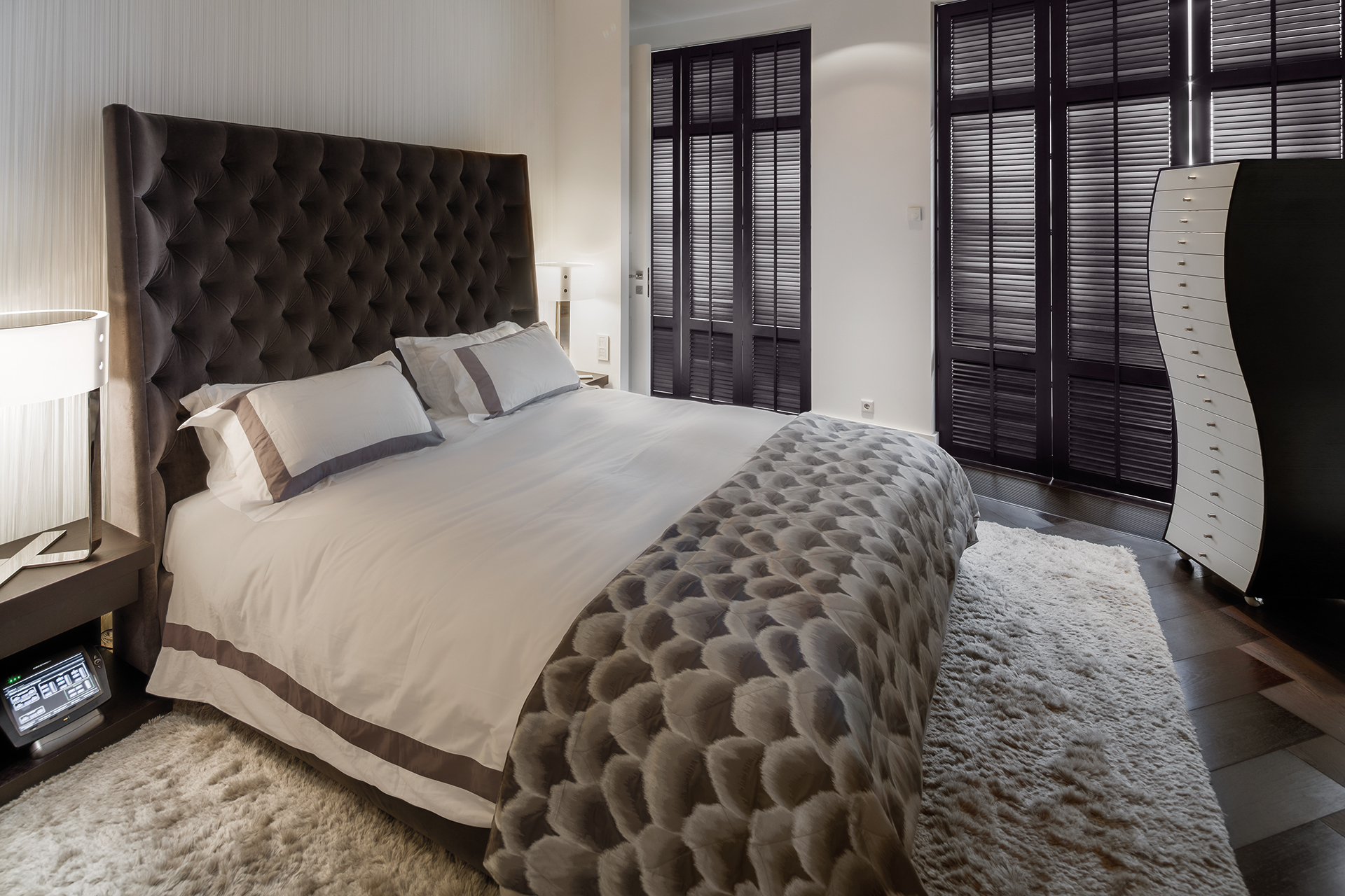 Master bedroom with a wavy cabinet and large headboard bed