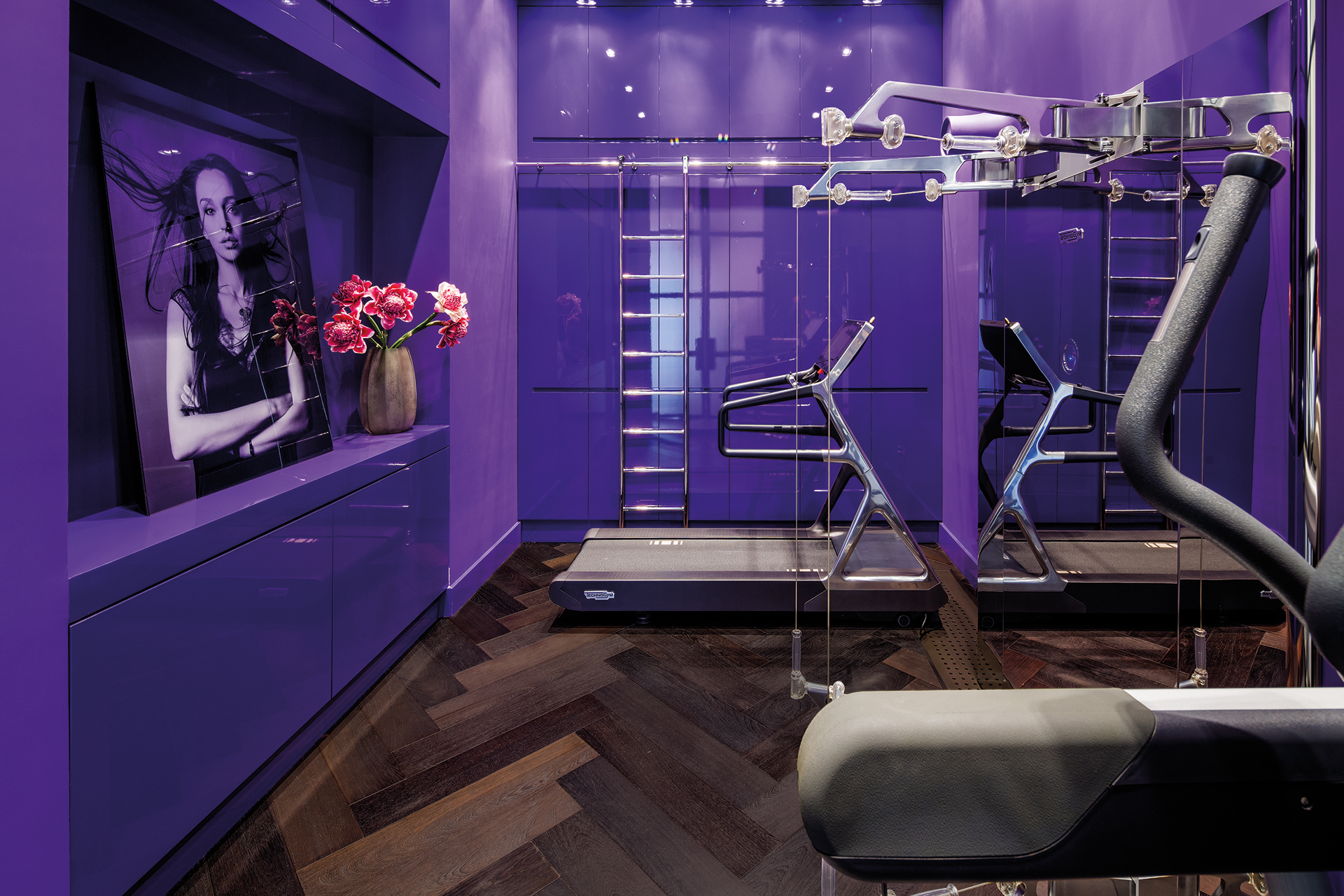 Home gym in purple with a treadmill and hometrainer