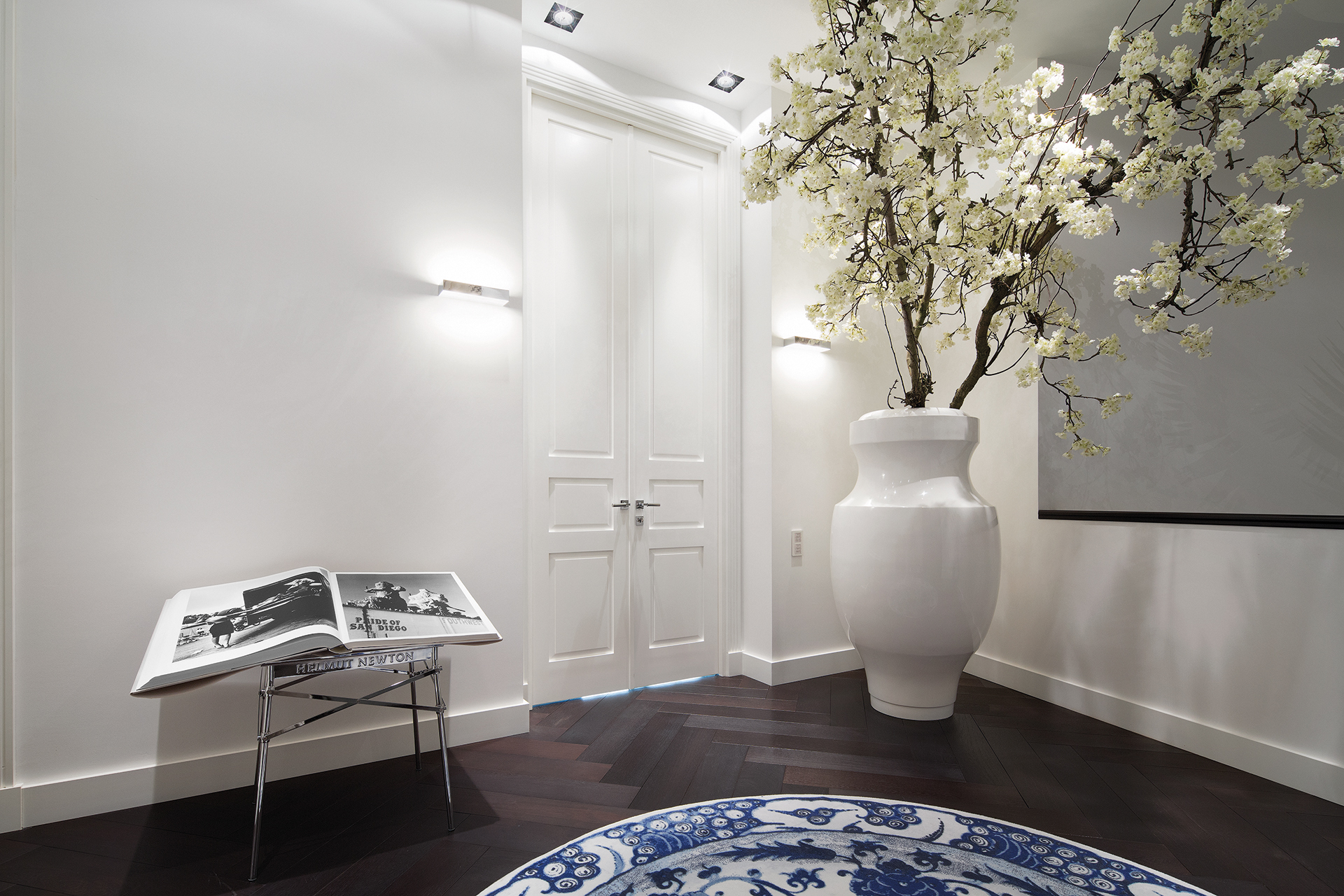 white hallway with circular carpet and bookstand