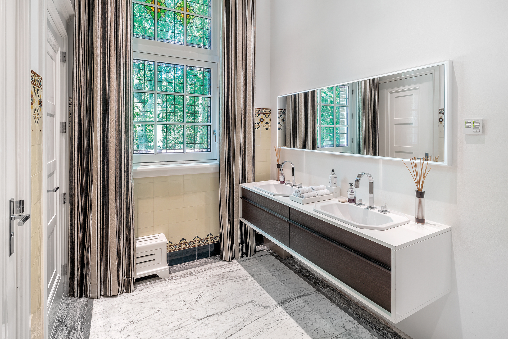 Restroom with marble floors and stained glass window the sink is wide and hanging with a wide continueous square mirror above