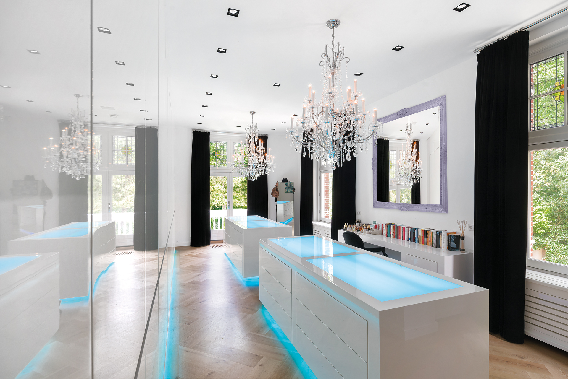 Modern wardrobe with overhead chandaliers and LED edgelighting on the cabinets