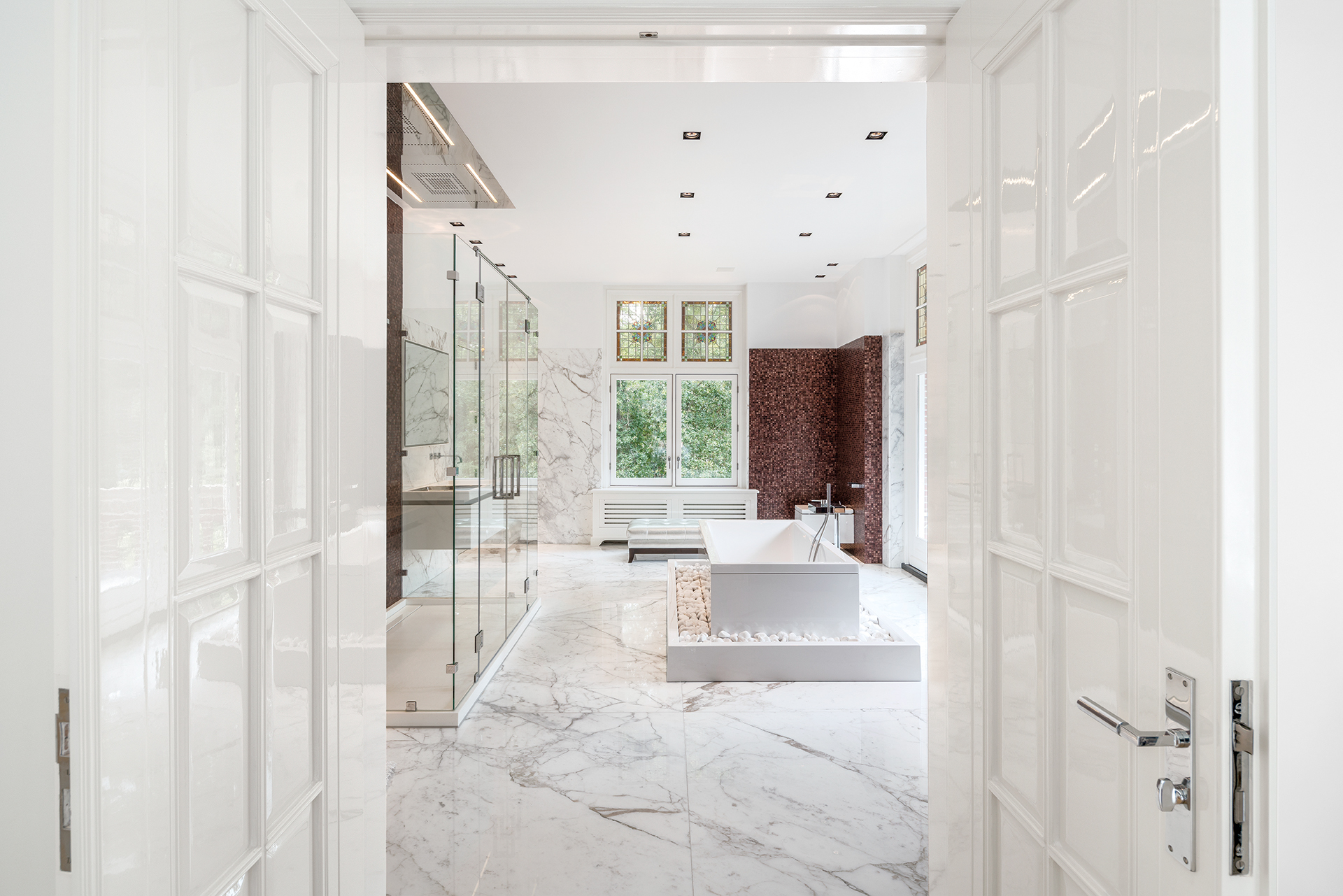 Side entrance to the master bathroom with full marble floor, mosiac and stained glass windows