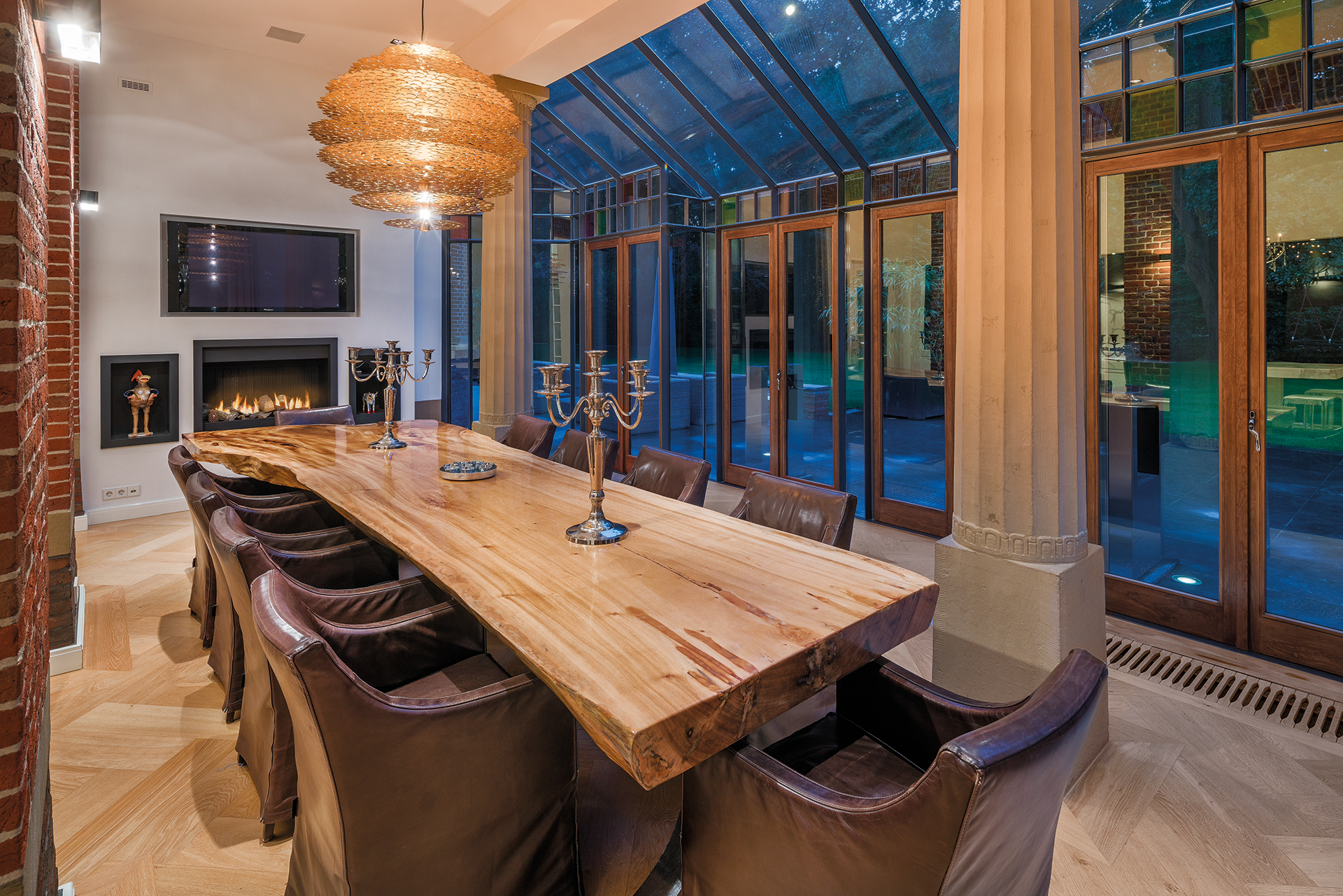 A large dining table from a tree trunk in a pillared foyer