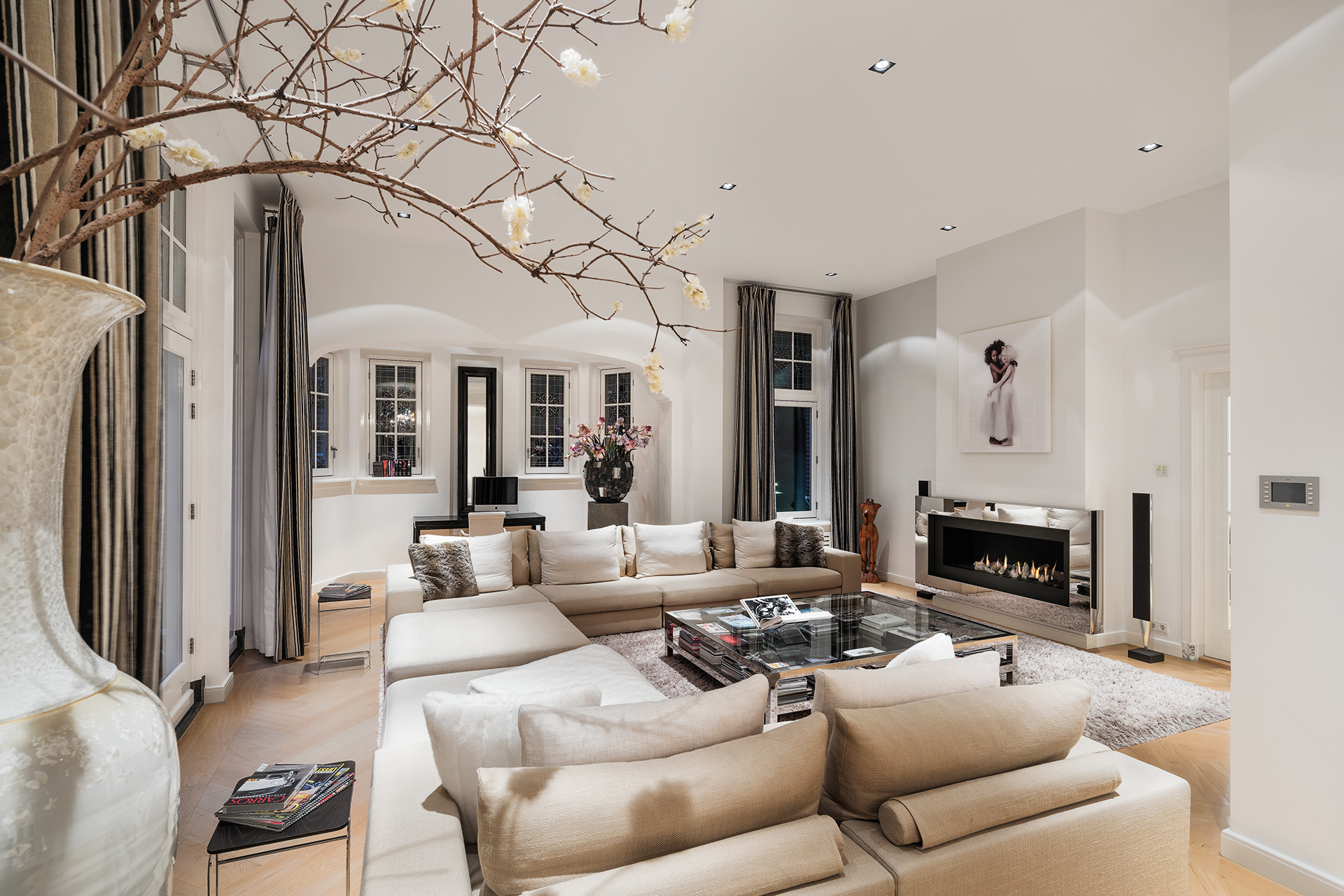 beige furnished living room with two large corner sofas around a modern fireplace