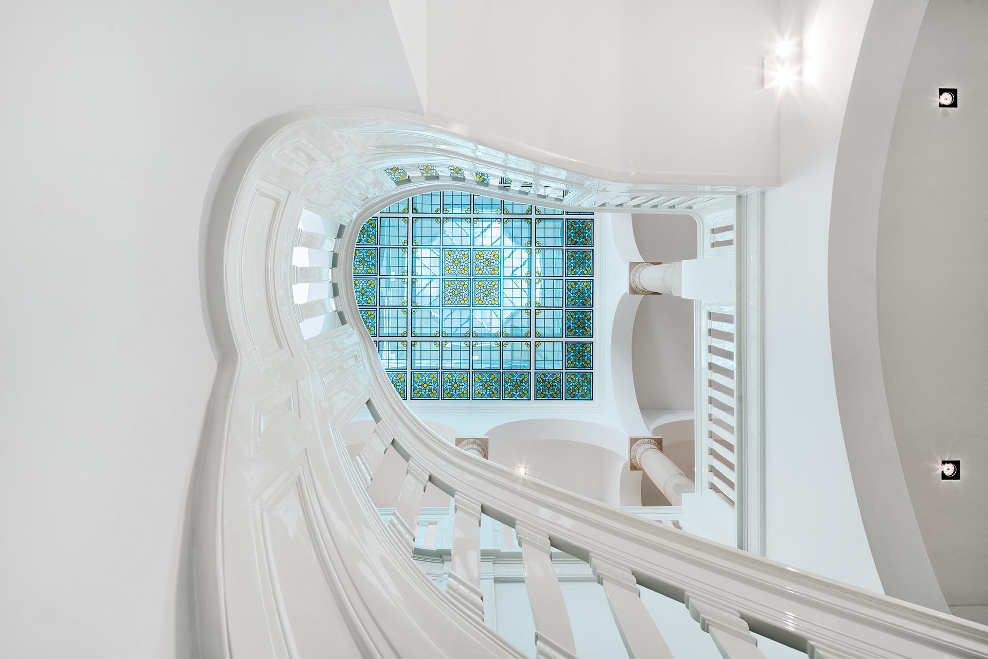 A staircase below a large stained glass ceiling with blue light radiating down