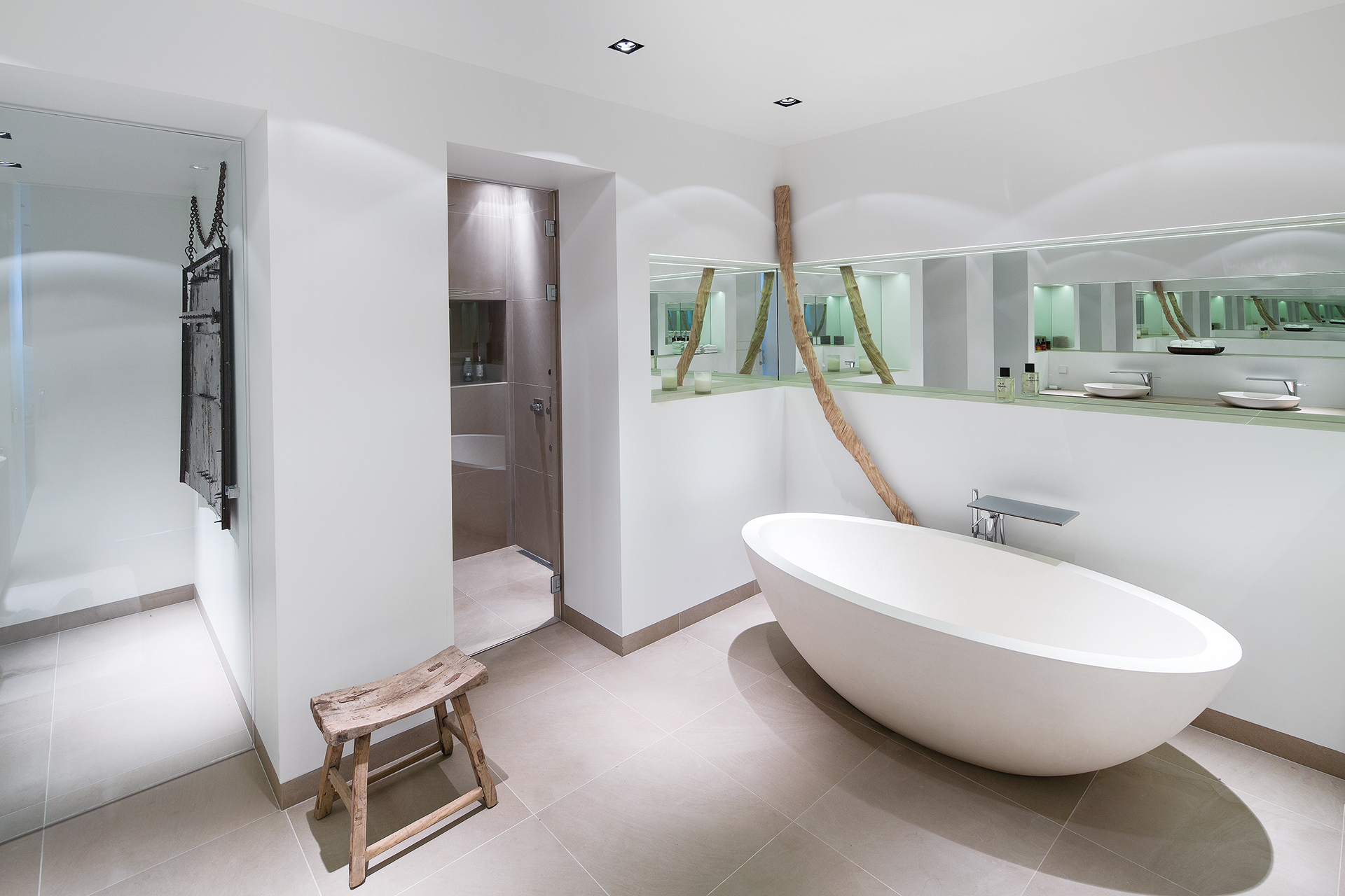 Master bathroom in white with mirrored wall list, bathtub and shower cabin