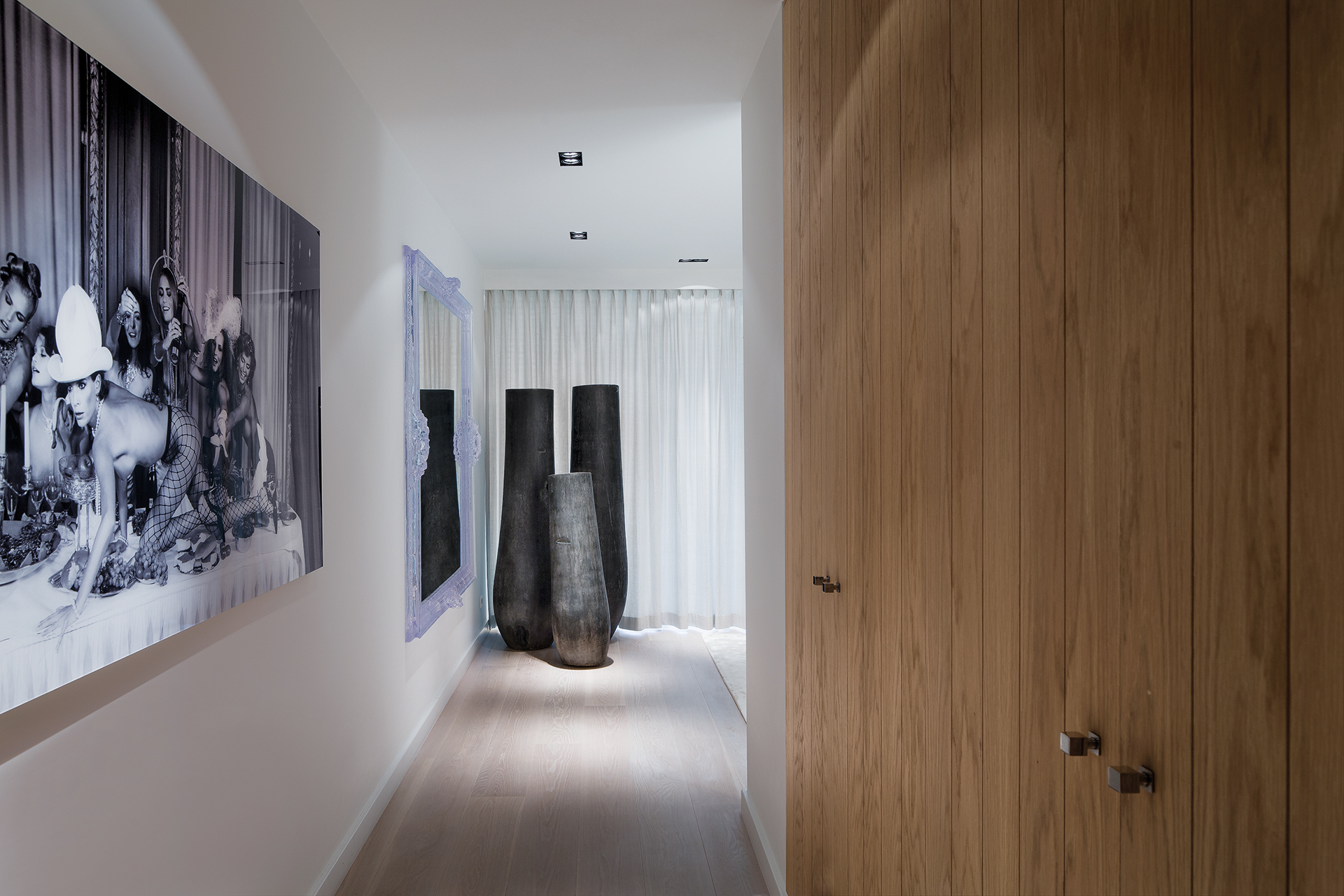 Hallway decorated with warm wooden stain flooring and a cobra art painting with earthern pottery at the end