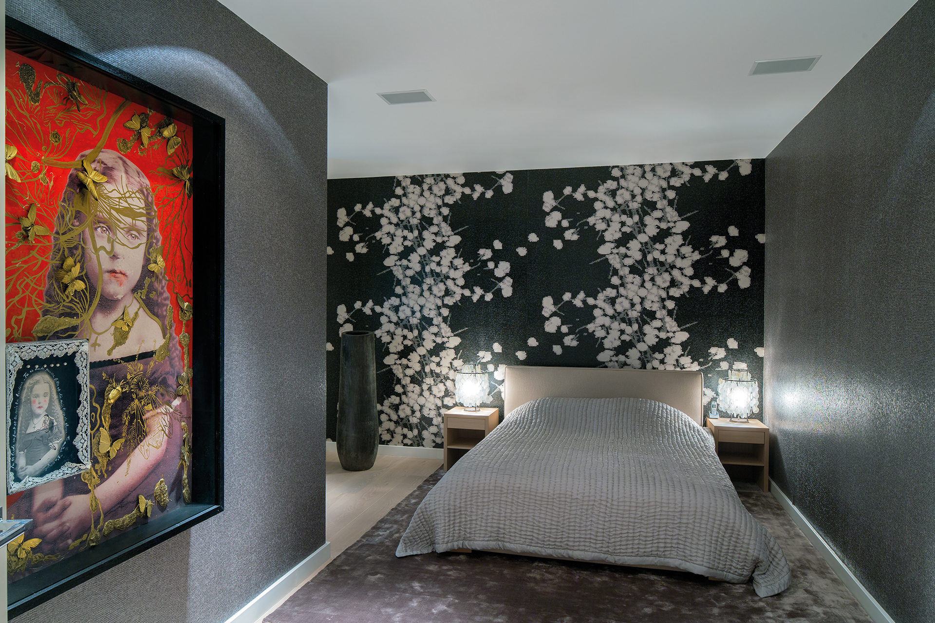 Floral wallpaper covers the walls of this bedroom with a saintly picture of a child
