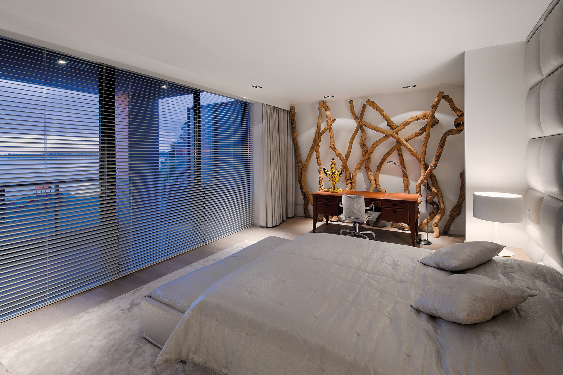 Master bedroom overlooking the observation deck and beach, gnarled driftwood adorns the back wall which seats a work area with desk.