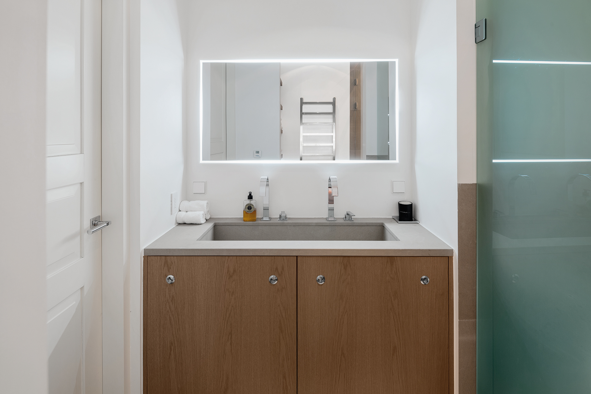 bathroom washtable with white stucco walls and a backlit mirror
