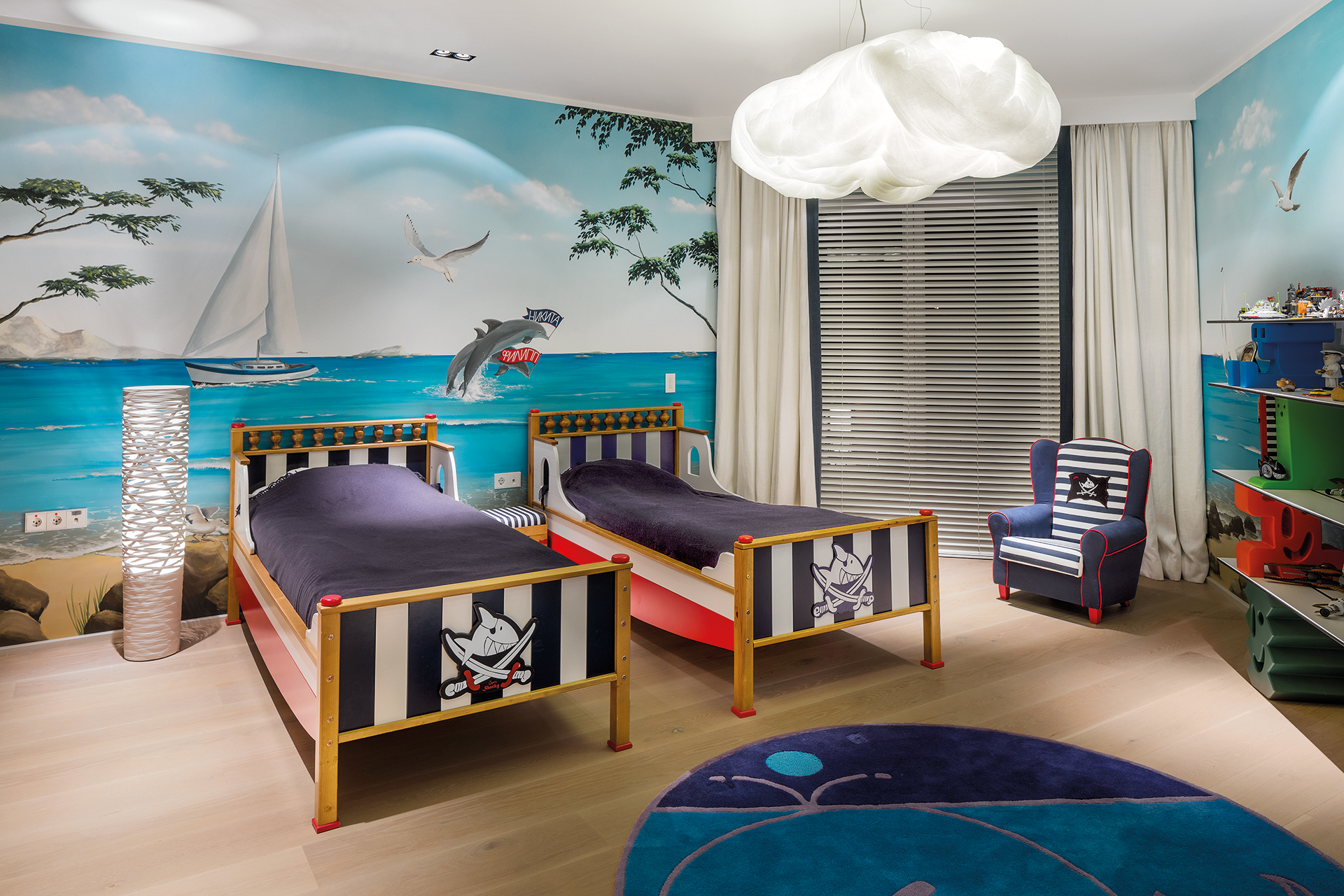 Sea themed wallpaper adorns the walls surrounding pirate themed beds