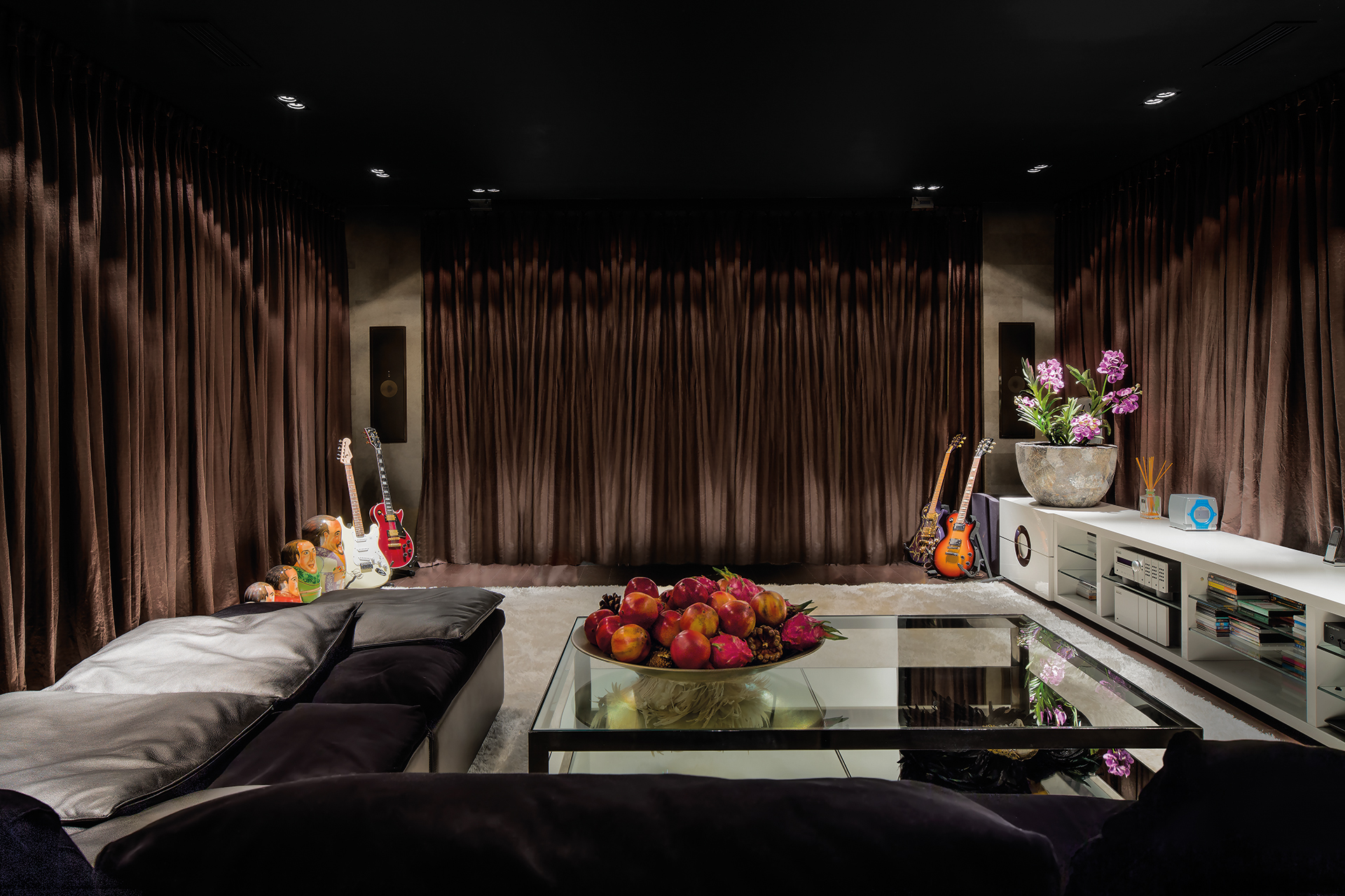 home cinema with retractable curtains over the silver screen a powerful soundsystem with amps and guitars flank the viewing area