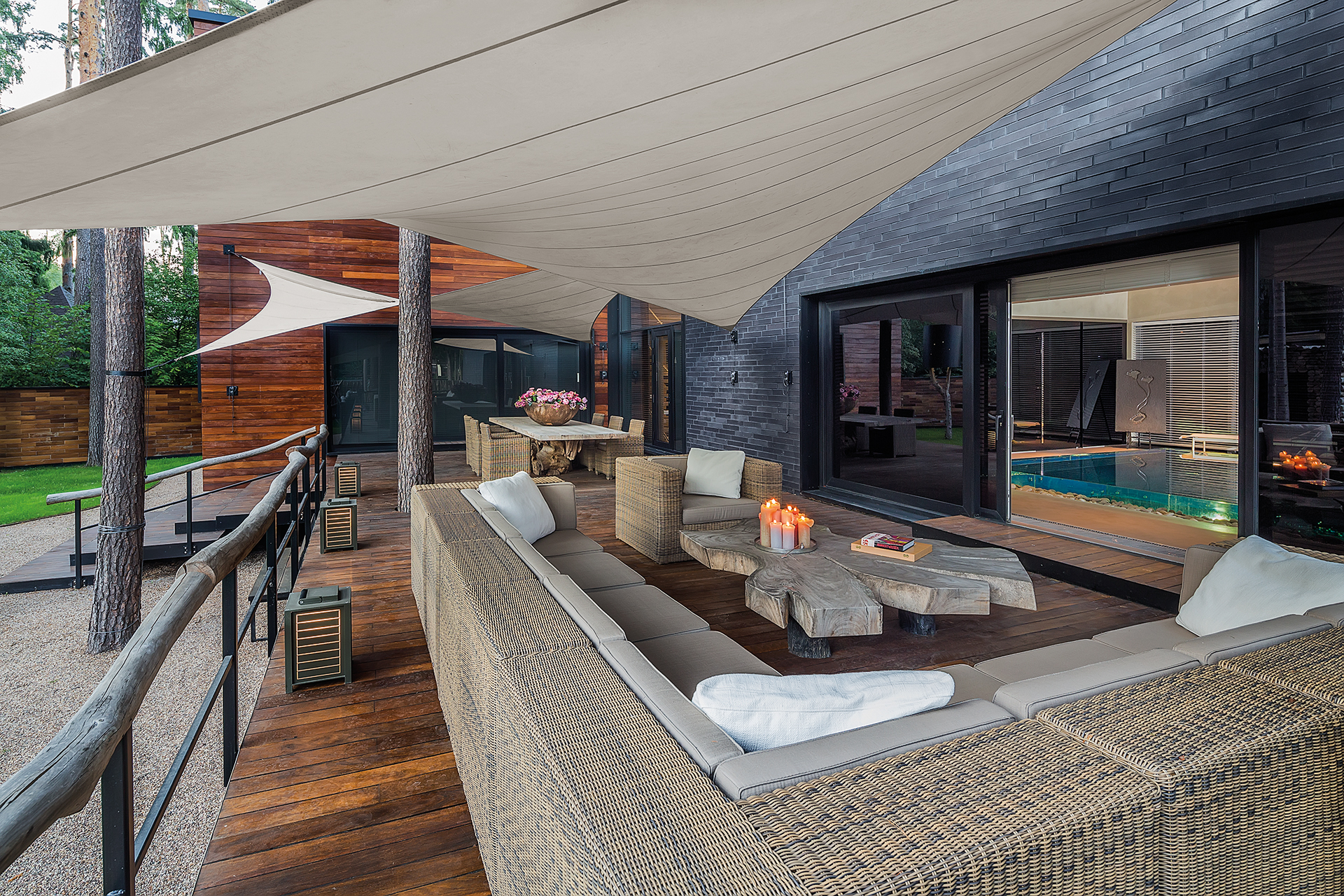 backyard patio with a tree trunk table and sail like parasols overhead