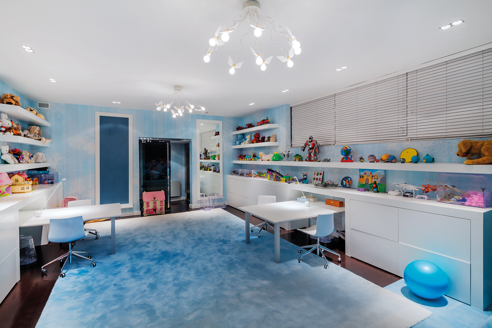 colorful toys line the walls in this playfully designed play room in sky blue