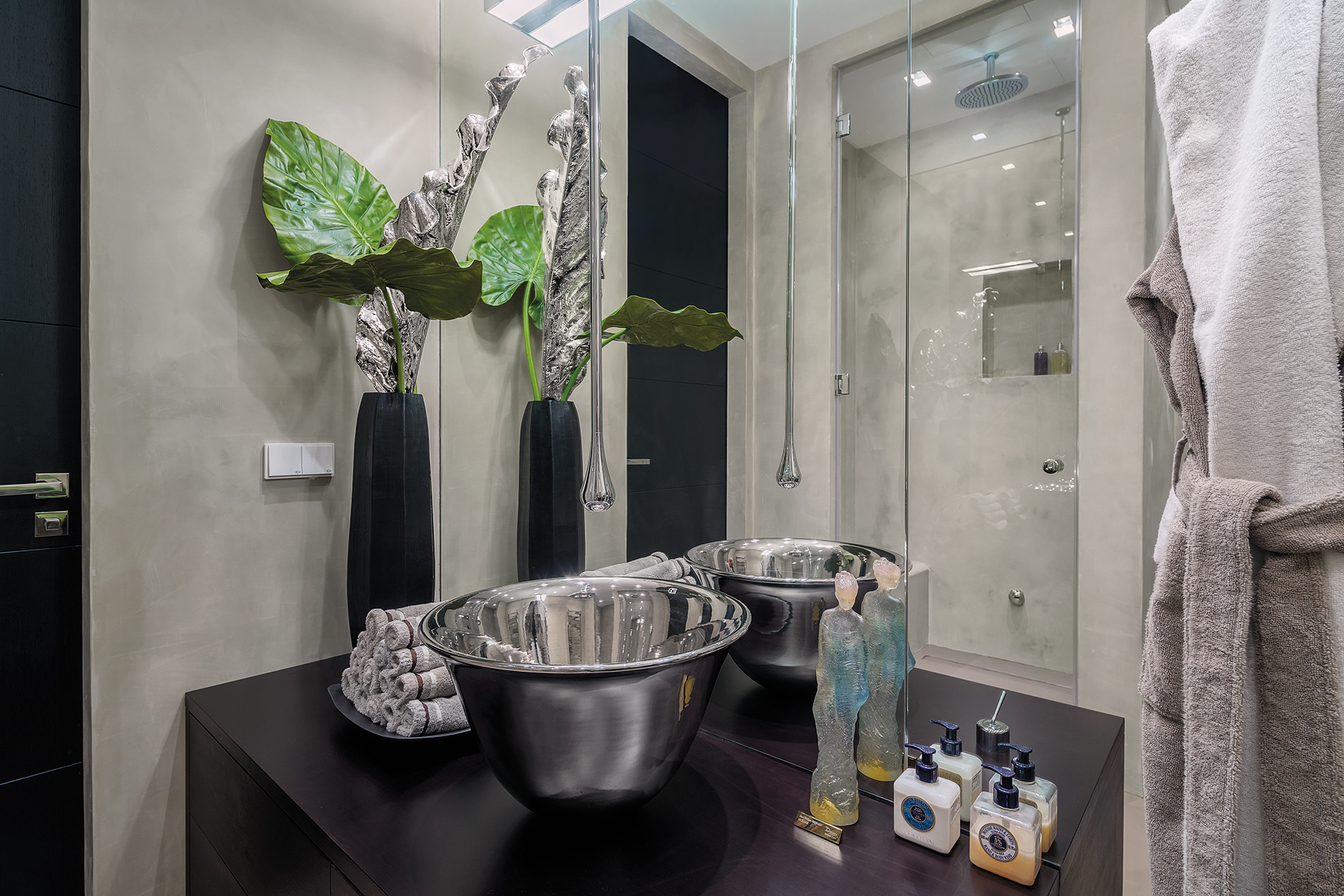 Sink with ceiling mounted silver spout infront of the shower with ceiling high mirrors