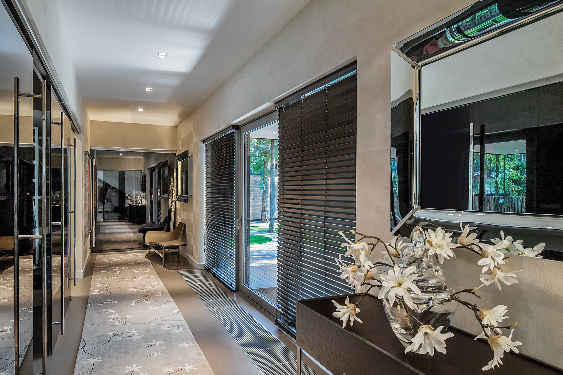 Hallway leading to the pool with blind covered doors leading outside