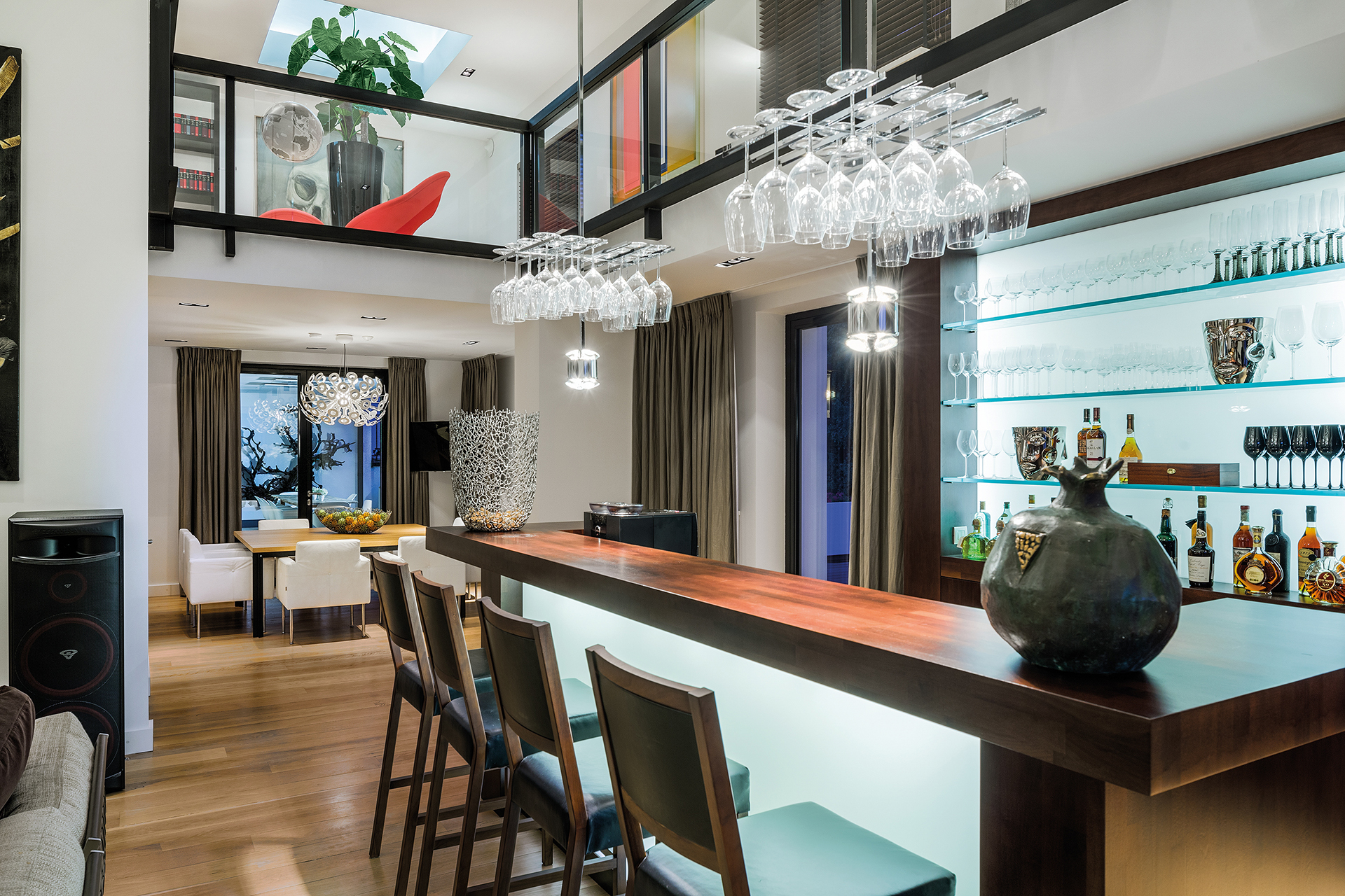 A home bar with lit drinks cabinet and overhanging glass holder