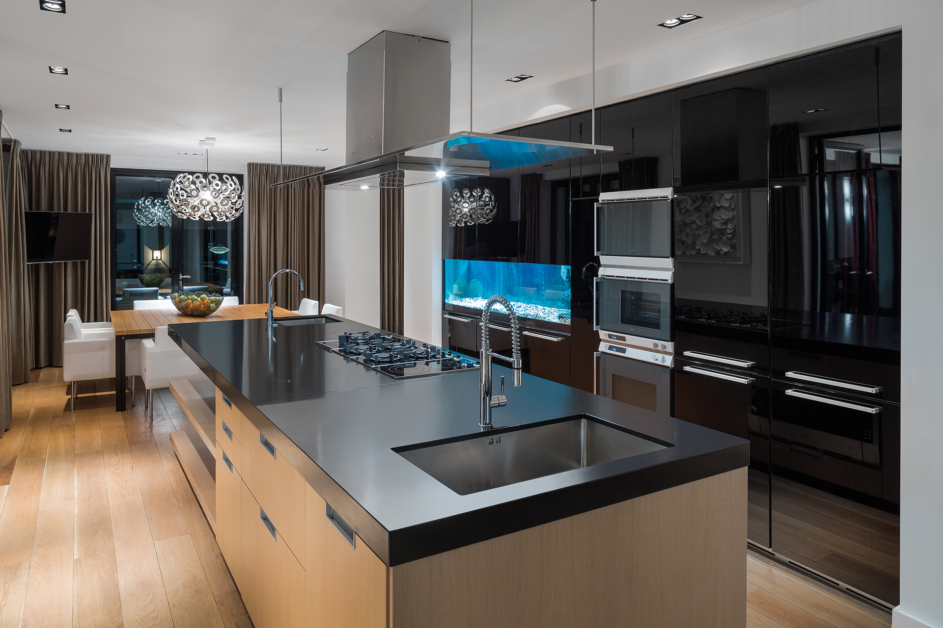 Modern kitchen with island and aquarium, a dinner space sits in the back