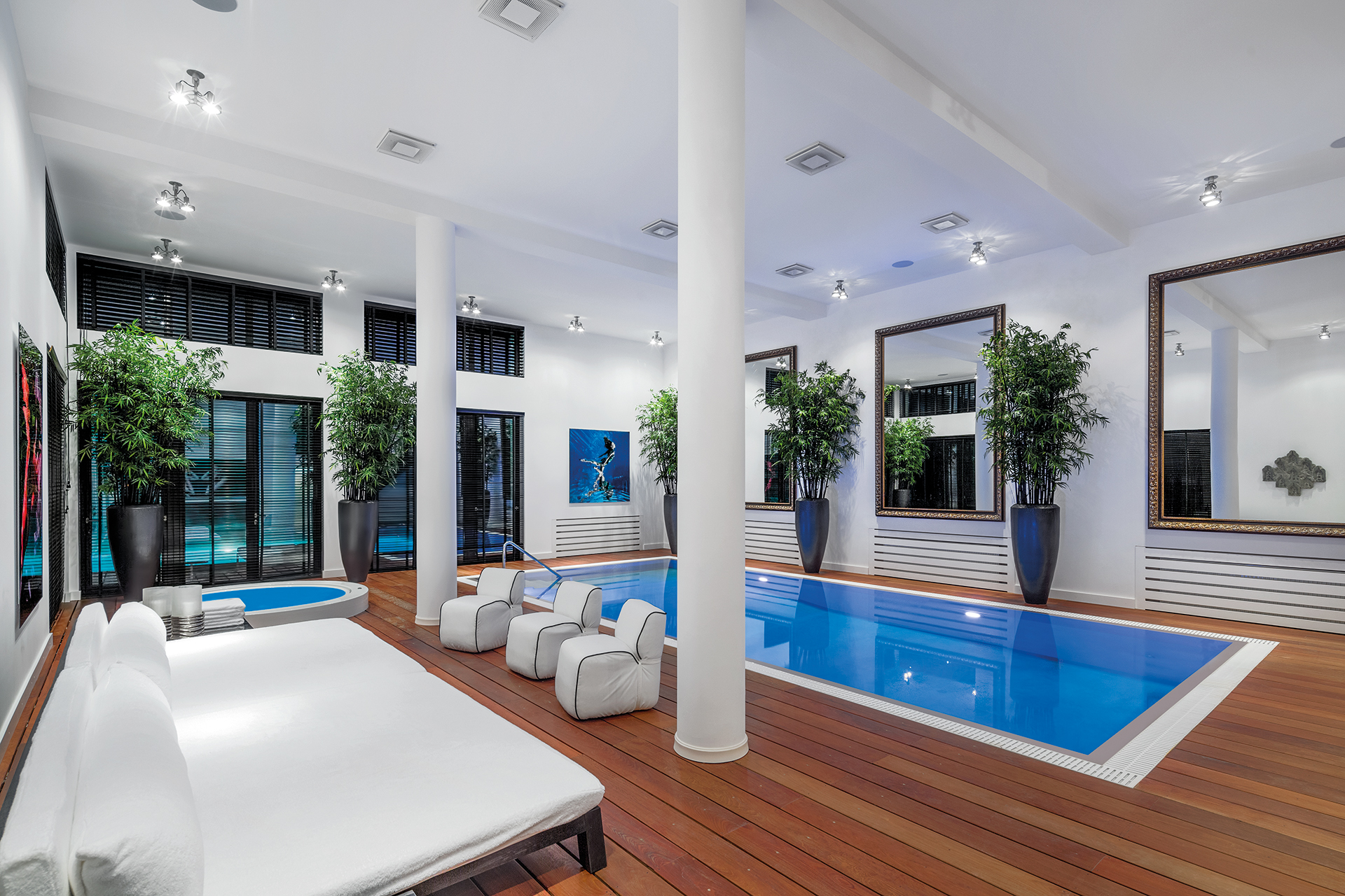 Indoor pool with surrounding deck and a Jacuzzi in the corner. Large mirrors and potted bamboos line the wall