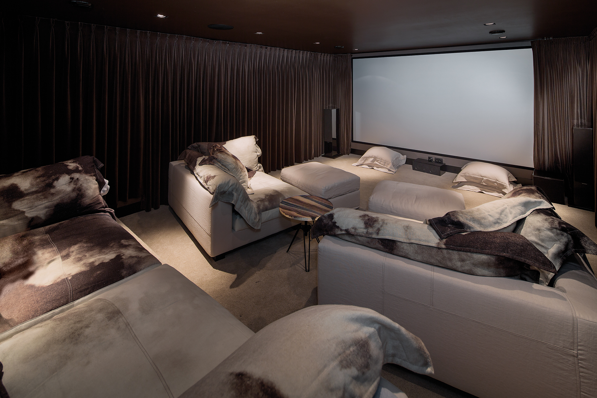 comfortable home cinema with multiple sofas and blankets