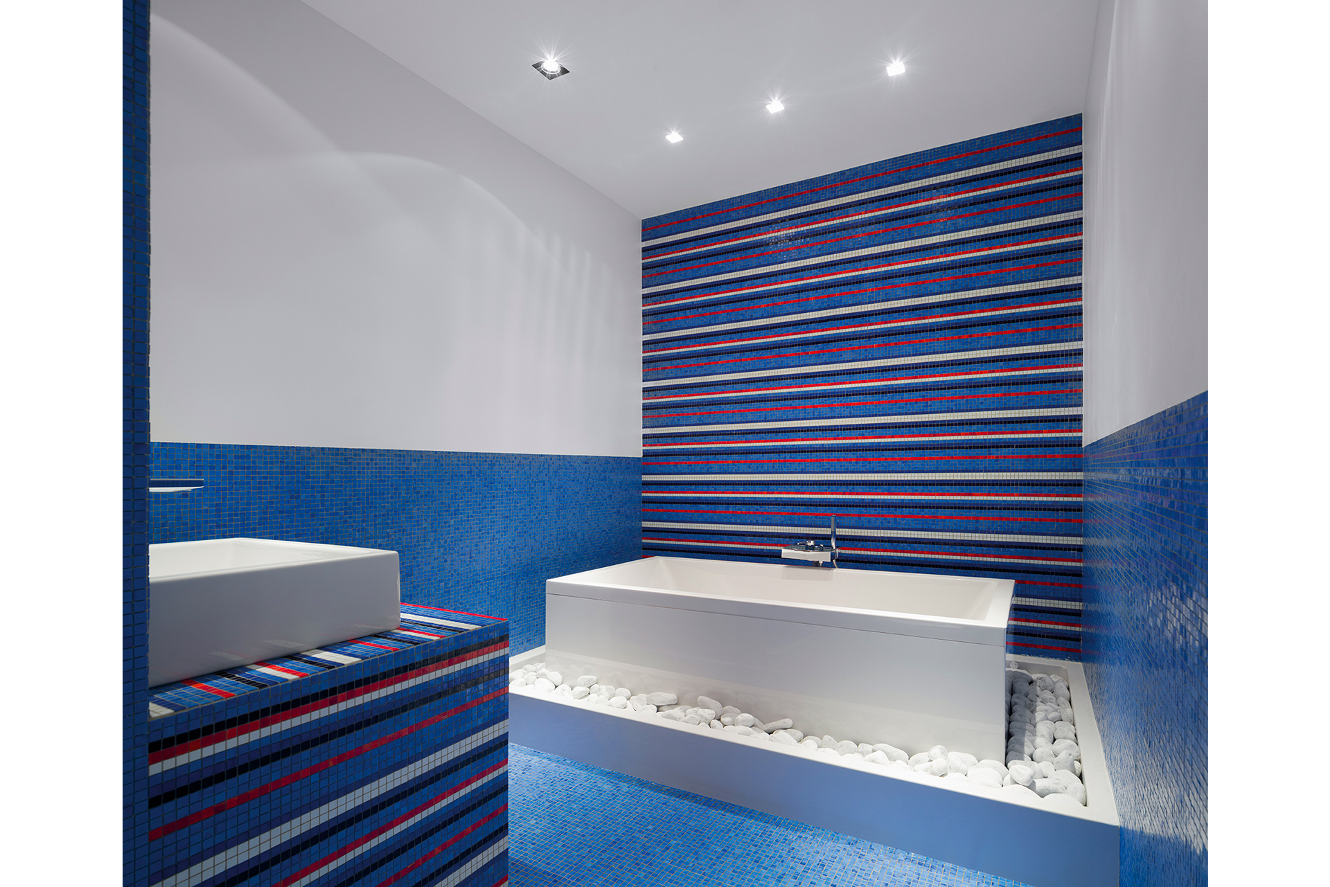 Blue mosiac covers the walls surounding a designer bathtub with natural stone overflow