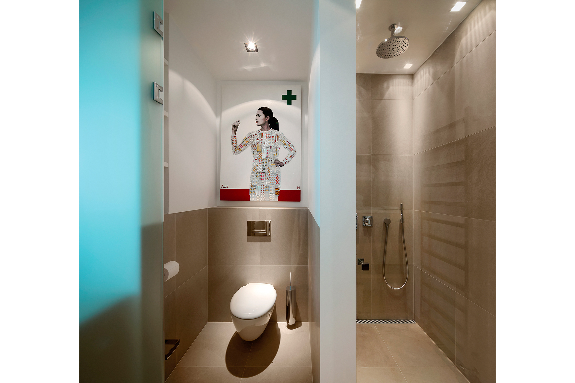 Bathroom with warm beige tiles housing a toilet and rain shower
