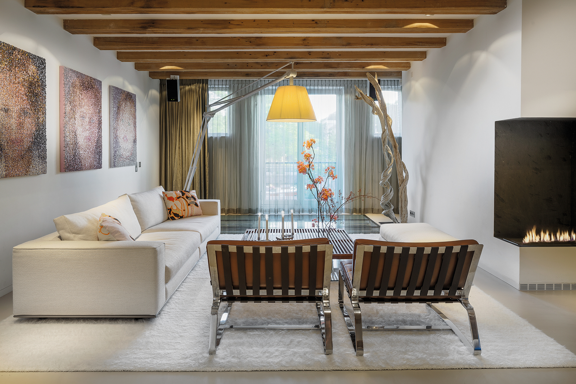 apartment corner with soft carpet large arching floor lamp and Jorge Quijano paintings